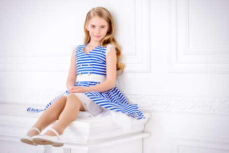 Leuk klein meisje in een mooie zomerse jurk poseren in een kamer met klassiek wit interieur. Kid's mode. Stockfoto