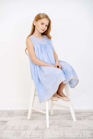 Beautiful little girl in a pale blue dress sitting on a chair in a white room full of light. Kid's fashion.