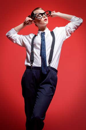 Mode schot. Aantrekkelijk vrouwelijk model poseren in een man's shirt en broeken met hangers en elegante vrouwelijke glazen. Man en vrouwen stijl kleding. Rode achtergrond. Stockfoto