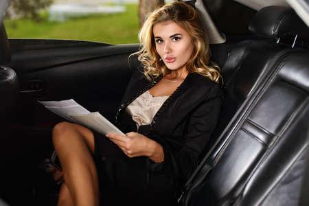 Portret van een mooie zakenvrouw met haar mobiele telefoon in een auto.