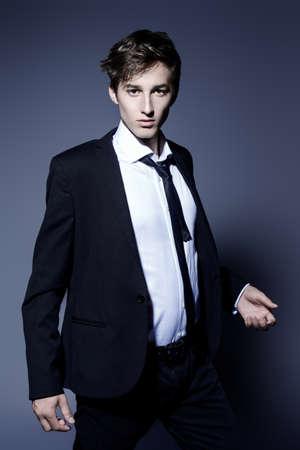 Fashion shot. Handsome young man posing in elegant black suit and white shirt. Studio shot.