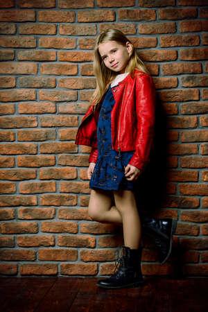 Modern acht jaar oud meisje poseren door de stenen muur. Stedelijke stijl kleding. Kindermode. Stockfoto