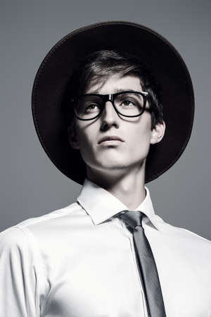 Fashion shot. Portrait of a handsome young man posing in white shirt and a hat. Studio shot.