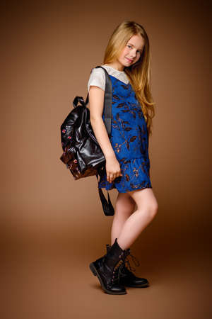 Children's fashion. Cute eight year old girl with long blonde hair posing in summer dress and a bag. Studio shot. Full length portrait. Archivio Fotografico