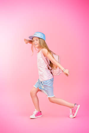 Childrens fashion. Cute eight year old girl wearing summer jeans clothes and a bag posing over pink background. Studio shot.