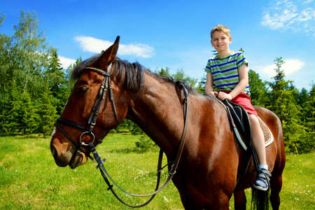 The boy is riding a horse in the park. Sunny summer day.