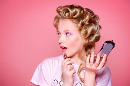 Portrait of a pretty girl teenager with curlers in her blonde hair painting lips with lipstick. Teen style, fashionable teen girl. Cosmetics and make-up. Imagens