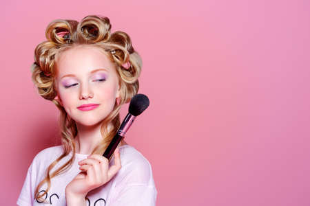 Portrait of a pretty girl teenager with curlers in her blonde hair and brushes. Teen style, fashionable teen girl. Cosmetics and make-up. Фото со стока - 80472981