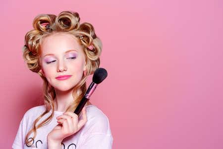 Portret van een mooie meisjestiener met krulspelden in haar blonde haar en borstels. Tiener stijl, modieus tienermeisje. Cosmetica en make-up.