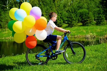 Happy boy is riding a bicycle with colored balloons in a park. Summer holidays. Birthday.