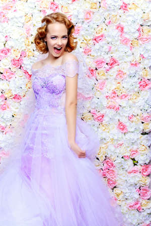 Exciting bride woman in a beautiful dress posing by a background of roses. Wedding fashion. Imagens