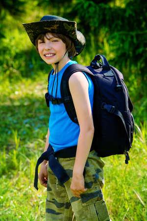 Tien jarige jongen gaat met rugzak en verrekijker wandelen. Verkennen van de wereld. Zomervakantie. Buitenactiviteiten.
