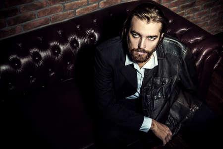 Ritratto di un bell'uomo elegante su un divano in pelle. Colpo di moda Abbigliamento e accessori per uomo. Archivio Fotografico - 80750930