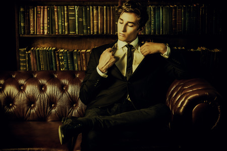 Handsome well-dressed young man by the bookshelves in a room with classic interior. Business style. Фото со стока