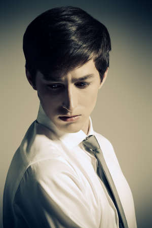 Serious young man in white shirt and a tie. Business style. Studio fashion shot.