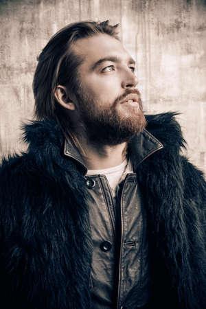 모피 코트를 입고 세련 된 잔인 수염 난된 남자의 패션 쐈어. 그런 지 배경 위에 촬영 스튜디오입니다.