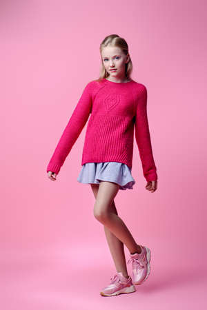 Full length portrait of a cute girl teenager over pink background. Studio shot. Teens fashion.