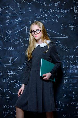 Education. Smart student girl wearing black school dress standing by a blackboard with a book. Chalkboard background.