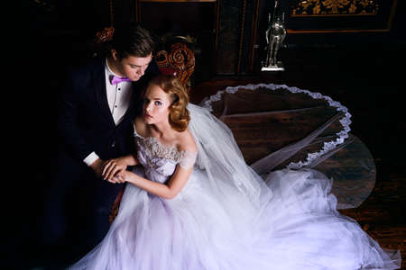 Beautiful bride and groom sitting in tender embrace at a luxurious apartments. Wedding fashion.
