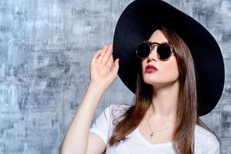 Close-up portret van een hipster meisje met hoed en ronde zonnebril. Schoonheid, cosmetica.