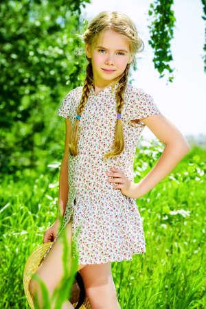 Mooi meisje in een lichte zomerjurk staat in een veld op het platteland.