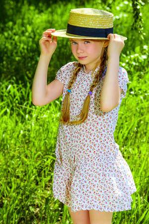 Hübsches Mädchen in einem leichten Sommerkleid steht auf einem Feld auf dem Lande. Standard-Bild - 81054687
