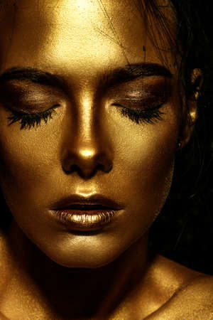 Beauty concept. Close-up portrait of a beautiful young woman with glowing golden skin. Skin care products, cosmetics. Jewellery concept. Stock Photo