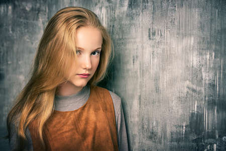 Portrait of a cute blonde girl teenager standing by a grunge wall. Stockfoto