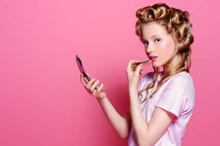 Portrait of a pretty girl teenager with curlers in her blonde hair painting lips with lipstick. Teen style, fashionable teen girl. Cosmetics and make-up. Foto de archivo