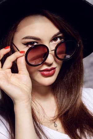 모자와 라운드 선글라스를 착용하는 hipster 소녀의 근접 초상화. 미용, 화장품.