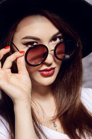 Close-up portrait of a hipster girl wearing hat and round sunglasses. Beauty, cosmetics. Stok Fotoğraf