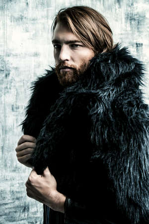 Fashion shot of a stylish brutal bearded man wearing fur coat. Studio shot over grunge background. Stock Photo