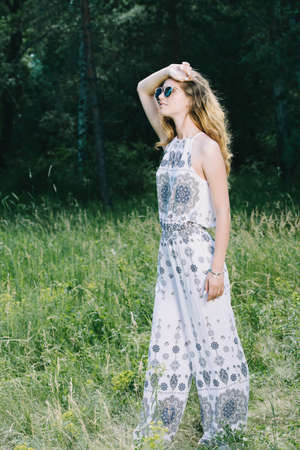 Beautiful romantic girl in a clearing in the forest. Modern hippie style. Beauty, fashion outdoor. Banco de Imagens