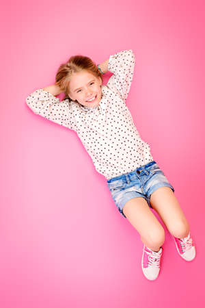 Happy childhood. Cute eight year old girl wearing summer jeans shorts and blouse lying on a pink floor. Studio shot.