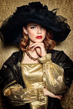 Portrait of a gorgeous young woman in elegant broad-brimmed hat and luxurious dress over golden background. Vintage style. Beauty, fashion. Stock Photo