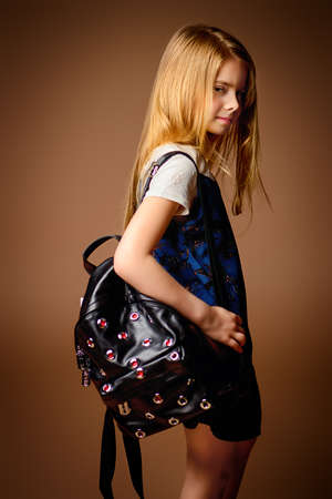 Childrens fashion. Cute eight year old girl with long blonde hair posing in summer dress and a bag. Studio shot.