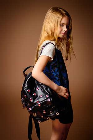 Kindermode. Leuk acht jaar oud meisje met lang blond haar poseren in zomerjurk en een tas. Studio shot. Stockfoto - 81369923