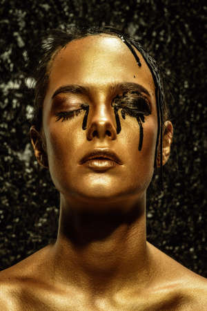 Beauty provocation. Body painting project. Portrait of a young woman with golden skin and black oil pouring on her. Fashionable provocation. Pollution and poisoning concept. Stock Photo