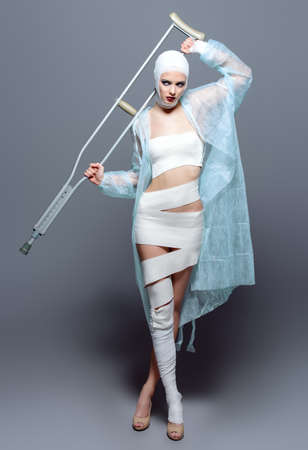 Fashion shot. Gorgeous female model in bandages and hospital gown posing at studio with crutches. Beauty and medicine, plastic surgery. Stockfoto