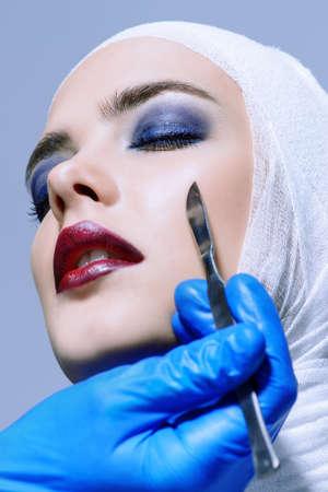 Bellezza, moda e medicina, chirurgia plastica. Ritratto di una giovane donna attraente in bende e abito ospedaliero. Studio shot. Archivio Fotografico - 81506184