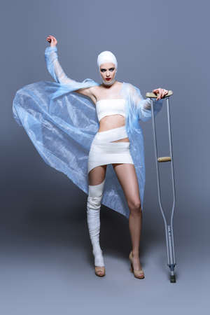 Fashion shot. Gorgeous female model in bandages and hospital gown posing at studio with crutches. Beauty and medicine, plastic surgery. Zdjęcie Seryjne