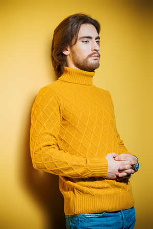 Handsome man wearing yellow pullover. Mens beauty, fashion. Hairstyle for men. Yellow background.