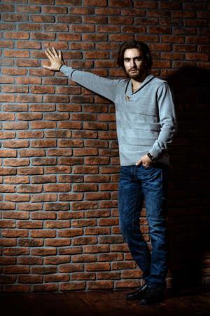 풀 오버와 청바지 벽돌 벽에 의해 서 입고 우아한 잘 생긴 젊은 남자의 전체 길이 초상화. 남자의 아름다움, 패션. 남성 이발소, 헤어 스타일.