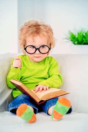 Kleine driejarige jongen in glazen leest sprookjes. Educatief concept.