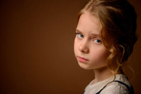 Portrait of a beautiful eight year old girl with calm pensive look. Stock Photo