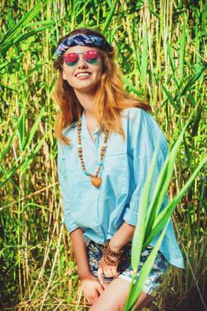 Beautiful hippie girl stands among the reeds in a summer sunny day. Spirit of freedom. Fashion shot. Bohemian, bo-ho style. Stok Fotoğraf - 81781554