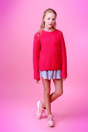 핑크 배경 위에 귀여운 소녀 십 대의 전체 길이 초상화. 스튜디오 촬영. 하이틴의 패션. 스톡 콘텐츠