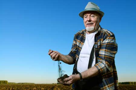 노인 농부는 소수의 비옥 한 검은 색 토양을 손에 들고 웃고 있습니다. 스톡 콘텐츠 - 81791666