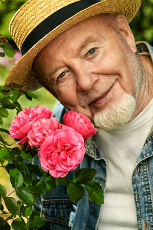 Portrait of a handsome senior man growing roses in his garden.