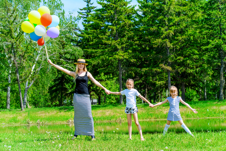 Cheerful mother runs with her little daughters with balloons through the park.